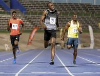 Usain Bolt (C) crosses the finish line first to win his first 200m race for the season with a time of 20.20 seconds next to Miguel Francis (L) and Nesta Carter (R) during the UTECH Classic 2015 at the National Stadium in Kingston, April 11, 2015. REUTERS/Gilbert Bellamy