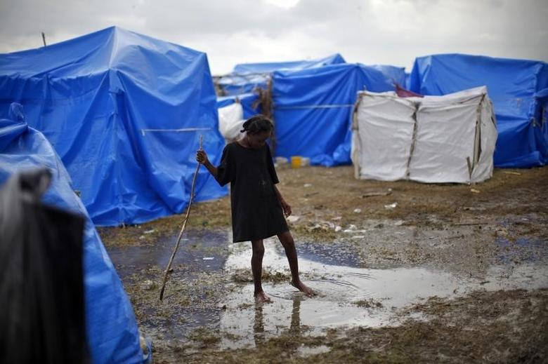 A girl crosses a puddle of water after heavy rains at a makeshift tent camp in Cite Soleil in Port-au-Prince in this file photo taken on February 26, 2010. REUTERS/Carlos Barria