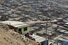 Dali Capuchay arroja agua desde su vivienda en Pamplona Alta en San Juan de Miraflores, Perú, mar 10 2015. Perú redujo la pobreza en 1,2 puntos porcentuales el año pasado, un ritmo menor frente a años previos, en medio de un freno en el crecimiento económico del país minero por la caída de los precios de las materias primas y una ralentización de las inversiones. REUTERS/Mariana Bazo