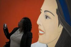 A woman takes a selfie photo with the 'Red Smile' by Alex Katz during the opening preview at The Whitney Museum of American Art in New York April 23, 2015. REUTERS/Brendan McDermid
