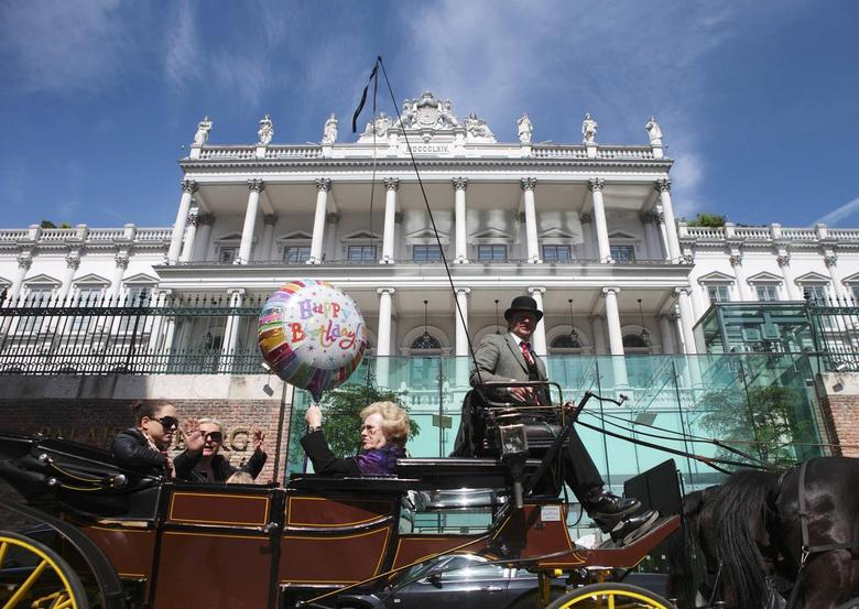 Passengers wave to journalists from a traditional Fiaker horse-carriage as they pass Palais Coburg hotel, the venue of nuclear talks in Vienna April 22, 2015. REUTERS/Heinz-Peter Bader