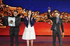 Mexican director Bernardo Arellano (R) raises a Tiantan Award trophy as he celebrates with cast members on the stage after winning the best film award, at the closing ceremony of the 5th Beijing International Film Festival in Beijing, April 23, 2015.  REUTERS/Stringer