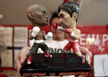A store employee holds up a stand with miniature figurines of boxers Manny Pacquiao (R) of the Philippines and Floyd Mayweather Jr. of the U.S., at a mall in Manila April 23, 2015. Pacquiao is scheduled to fight Mayweather on May 2, 2015 in Las Vegas, Nevada. REUTERS/Romeo Ranoco