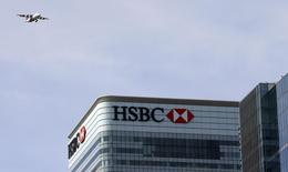 A plane flies past the HSBC building in Canary Wharf, London April 17, 2015. REUTERS/Cathal McNaughton