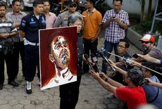 Todung Mulya Lubis, lawyer for two Australians facing the death penalty, Myuran Sukumaran and Andrew Chan, holds a self-portrait painted by Sukumaran at Wijayapura port in Cilacap, Indonesia, April 27, 2015. REUTERS/Beawiharta
