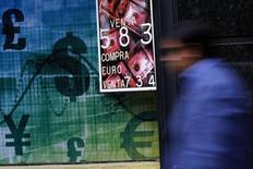 Una persona pasa frente a una casa de intercambio de monedas en Santiago, oct 30 2014. Las monedas de América Latina esperan esta semana los indicios que pueda dar la Reserva Federal de Estados Unidos sobre el momento específico en el que gatillará la esperada subida de tasas de interés, y las cifras de la evolución del Producto Interno Bruto (PIB) del país en el primer trimestre.  REUTERS/Ivan Alvarado