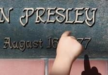 A child points at a plate with Elvis Presley's name during a Presley memorial event in Tokyo August 12, 2007.    REUTERS/Issei Kato