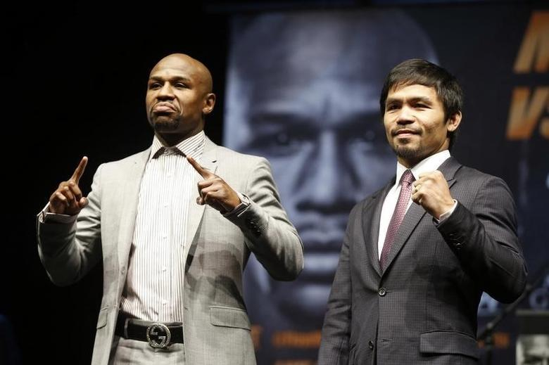 Eleven-time, five-division world boxing champion Floyd ''Money'' Mayweather (L) and eight-division world champion Manny ''Pac-Man'' Pacquiao pose at a news conference ahead of their upcoming bout, in Los Angeles, California March 11, 2015.  REUTERS/Lucy Nicholson