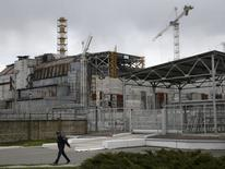A man walks in front of the sarcophagus covering the damaged fourth reactor at the Chernobyl nuclear power plant April 21, 2015. Ukraine will mark the 29th anniversary of the Chernobyl disaster, the world's worst civil nuclear accident, on April 26.  REUTERS/Valentyn Ogirenko