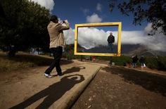 Visitors pose for pictures against Table Mountain at a viewing site in Cape Town, South Africa, April 29, 2015.  REUTERS/Mike Hutchings