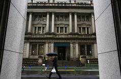En la imagen, un hombre pasa junto a un edificio del Banco de Japón en Tokio el 18 de febrero de 2015. El Banco de Japón recortó el jueves sus previsiones de precios al consumidor y aplazó de nuevo el plazo para alcanzar una ambiciosa meta de inflación, pero se abstuvo de ampliar su programa de estímulo, esperando que una recuperación de la economía impulse gradualmente a los precios. REUTERS/Thomas Peter