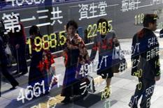 Women wearing Hakama, or Japanese traditional Kimono, are reflected in an electronic board, showing various stock prices, outside a brokerage in Tokyo, March 23, 2015. REUTERS/Yuya Shino