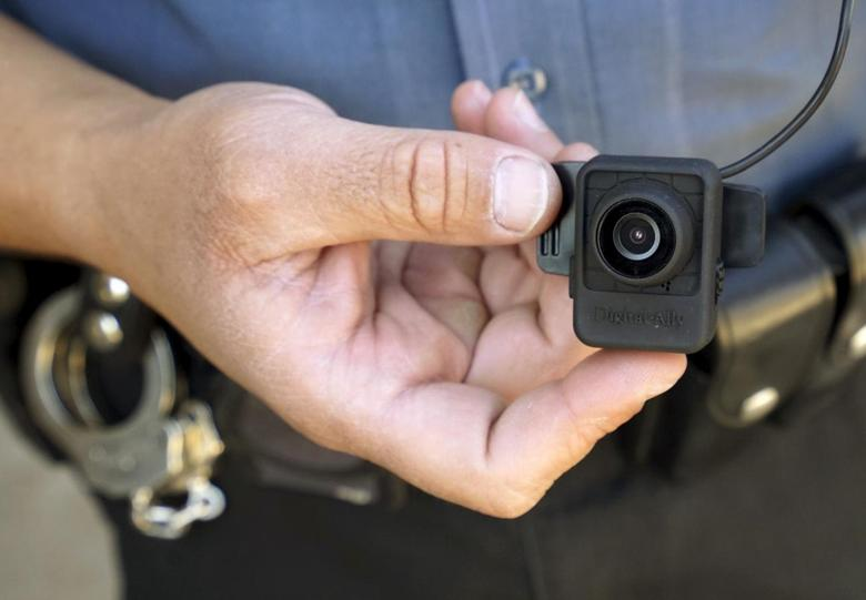 A Colorado Springs police officer poses with a Digital Ally First Vu HD body worn camera outside the police department in Colorado Springs April 21, 2015. REUTERS/Rick Wilking