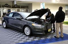 Workers prepare a 2015 Ford Fusion hybrid car for display at the International Consumer Electronics show (CES) in Las Vegas, Nevada, January 5, 2015. REUTERS/Rick Wilking