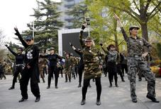 Seventy-nine-year-old Wang Baorong (C), dressed in military style clothes, and other participants perform square dancing at a park square in Beijing, China, April 9, 2015. REUTERS/Kim Kyung-Hoon