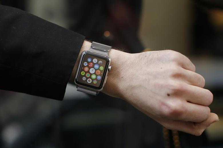 A customer presents his Apple Watch after buying it at a store in Paris, France, April 24, 2015. The Apple Watch goes on sale around the world on Friday, the final stage of a protracted launch of Apple Inc Chief Executive Tim Cook's first new product, capping months of publicity and a frenetic two weeks of pre-orders. REUTERS/Benoit Tessier - RTX1A46U
