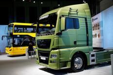 Bus Scania et campion hybride MAN lors de la conférence de presse annuelle de Volkswagen. Le constructeur va créer une nouvelle structure regroupant ses divisions de camions MAN et Scania dans le cadre de ses efforts pour devenir le premier constructeur européen de poids lourds. Cette nouvelle entité, Truck & Bus GmbH, coordonnera la stratégie des deux marques, y compris en ce qui concerne les achats, le développement et les ressources humaines. /Photo prise le 12 mars 2015/REUTERS/Fabrizio Bensch