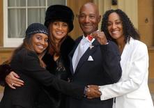 Cantor Errol Brown posa com sua família no Palácio de Buckingham após receber honraria de tornar-se Membro do Império Britânico. 27/11/2003.   REUTERS/Fiona Hanson