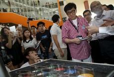 Singapore's new anti-drug ambassador, actor Jackie Chan looks at an exhibit of different types of drugs after launching an anti-drug mobile game application at Nanyang Polytechnic in Singapore May 7, 2015. REUTERS/Edgar Su