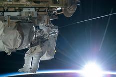 El astronauta de la NASA, Terry Virts, ingeniero de vuelo de la Expedición 42, se ve trabajando mientras el sol comienza a salir sobre el horizonte de la tierra, 21 de febrero de 2015. Tal vez no sean los desechos espaciales, asteroides errantes, escasez de suministros, un fallo de propulsión o hasta los malignos extraterrestres mostrados en tantas películas de Hollywood lo que desbarate una misión a Marte. Podrían ser los rayos cósmicos. REUTERS/NASA/Handout/Files
