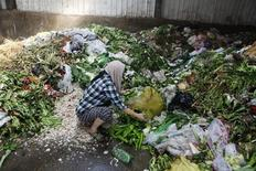 A woman picks up vegetables discarded by food vendors at a garbage dump site of a wholesale market in Xi'an, Shaanxi province July 27, 2014.  REUTERS/Stringer
