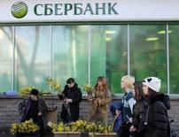 Женщины торгуют цветами у отделения Сбербанка в Ставрополе. 6 марта 2015 года. Крупнейший госбанк РФ Сбербанк сократил чистую прибыль за четыре месяца 2015 года, рассчитанную по российским правилам бухгалтерского учета, в 2,7 раза до 48,8 миллиарда рублей, сообщил банк. REUTERS/Eduard Korniyenko