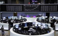 Traders are pictured at their desks in front of the DAX board at the Frankfurt stock exchange, Germany, May 8, 2015.     REUTERS/Remote/Staff