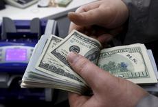 Un empleado cuenta dólares en una casa de cambios en Estambul, abr 15 2015. El dólar caía el martes frente al euro, después de que un alza en los rendimientos de los bonos alemanes opacó un aumento similar en los retornos de los papeles del Tesoro estadounidense, generando una demanda de monedas europeas.REUTERS/Murad Sezer