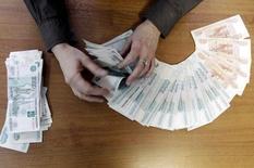 Сотрудница ставропольской компании считает рубли. Ставрополь, 17 декабря 2014 года. Рубль обновил максимум текущего года в паре с долларом, отправив его на уровень 49,27 впервые с конца ноября на фоне дорожающей нефти, а также в надежде на снижение конфронтации России с Западом и на рост продаж экспортной выручки в налоговый период. REUTERS/Eduard Korniyenko