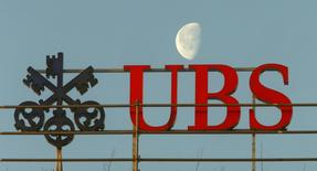 A file picture shows the waning moon behind a logo of Swiss bank UBS in Zurich, Switzerland February 10, 2015. REUTERS/Arnd Wiegmann/Files