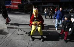 A child laughs as he walks past a man, who poses for photos for tips and is dressed like Homer Simpson in a Christmas outfit, sitting on a bench while counting his money on a chilly afternoon in New York November 2, 2014.    REUTERS/Carlo Allegri