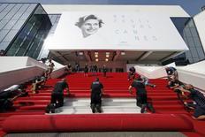 """Trabajadores instalan la alfombra roja en frente de la entrada principal del Festival Palace, para la ceremonia inaugural del sexagésimo octavo Festival de Cannes, en Cannes, Francia, 13 de mayo de 2015. El festival de cine más importante del mundo está a punto de comenzar en Cannes, con una mezcla de talento de estrellas, cine de autor y éxitos de Hollywood, aunque su director estaría más contento si la """"selfie"""" no se hubiera inventado jamás. REUTERS/Benoit Tessier"""