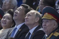 Президент России Владимир Путин и председатель КНР Си Цзиньпин на военном параде в Москве. 9 мая 2015 года.  Российские военные во второй половине года примут участие в учениях с армиями Китая, Индии, Монголии и не входящих в НАТО соседей по бывшему СССР, которые надеются также на военную помощь Запада. REUTERS/Host Photo Agency/RIA Novosti
