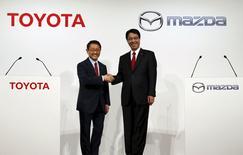 El presidente de Toyota, Akio Toyoda (Izquierda) y el presidente de Mazda, Masamichi Kogai (Derecha), se dan la mano durante una conferencia de prensa, en Tokyo, 13 de mayo de 2015. Toyota Motor Corp y Mazda Motor Corp anunciaron un plan para una asociación a largo plazo que vaya más allá de las relaciones basadas en proyectos ya existentes, en momentos en que la industria enfrenta crecientes costos y desafíos técnicos incluyendo requisitos ambientales y de seguridad. REUTERS/Issei Kato