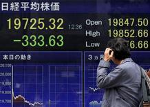 Un peatón se rasca la cabeza y mira un tablero electrónico que muestra el índice Nikkei de la Bolsa de Tokyo, en Tokyo, Japón, 30 de abril de 2015. El índice Nikkei de la bolsa de Tokio cayó el jueves a un mínimo en casi una semana luego de que otro aumento en los rendimientos de los bonos globales inquietó al mercado. REUTERS/Yuya Shino