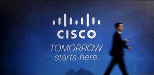 Un visitante camina junto a un panel publicitario de Cisco, en el Congreso Mundial de Móviles, en Barcelona, 27 febrero de 2014. La utilidad trimestral de Cisco Systems Inc superó por poco las estimaciones, debido a que la demanda por nuevos conmutadores, routers, equipos inalámbricos y servidores compensó un débil gasto en telecomunicaciones de sus clientes y bajas ventas en los mercados emergentes. REUTERS/Albert Gea/Files