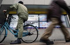 Un hombre en bicicleta mira a un tablero electrónico que muestra el índice Nikkei de la Bolsa de Tokyo, 24 de febrero de 2015. Las bolsas de Asia subían el viernes, en camino a un sólido avance semanal, mientras los inversores esperan unos datos de Estados Unidos más tarde en la sesión en busca de pistas sobre el momento en que la Reserva Federal de Estados Unidos subirá las tasas de interés. REUTERS/Yuya Shino