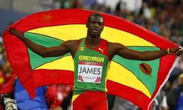 Kirani James of Grenada holds his national flag as he celebrates after winning the men's 400 metres at the 2014 Commonwealth Games in Glasgow, Scotland, July 30, 2014. REUTERS/Phil Noble