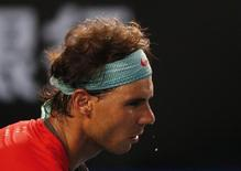 Drops of sweat fall from Rafael Nadal (L) of Spain as he serves to Roger Federer of Switzerland during their men's singles semi-final match at the Australian Open 2014 tennis tournament in Melbourne January 24, 2014.  REUTERS/Petar Kujundzic