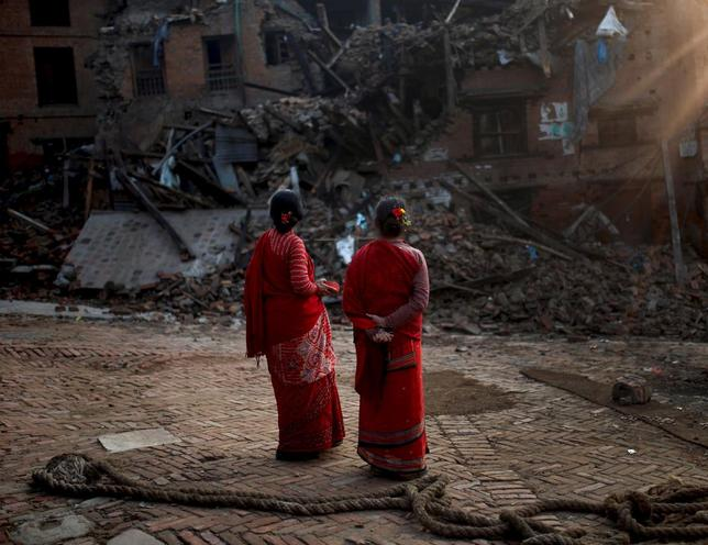 Women look at a collapsed building caused by earthquakes, in  Bhaktapur, Nepal, May 18, 2015. REUTERS/Ahmad Masood
