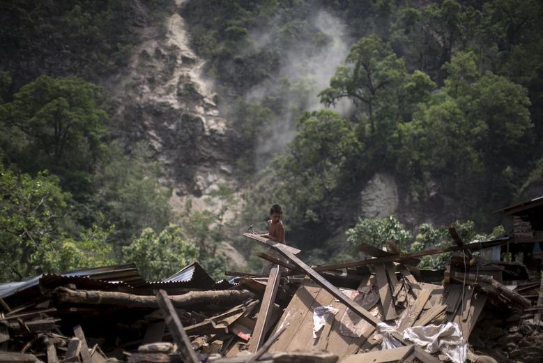 A boy clears rubble from his home during a landslide after Tuesday's earthquake at Singati Village, in Dolakha, Nepal, May 15, 2015. Picture taken May 15. REUTERS/Athit Perawongmetha