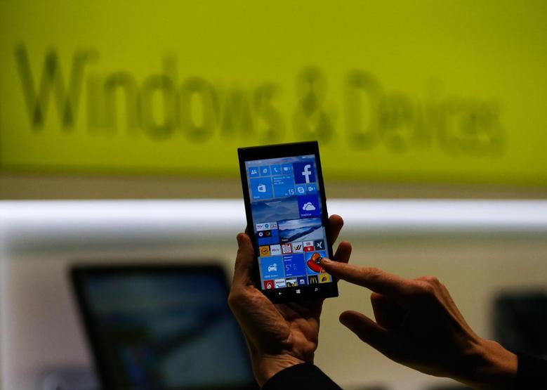 A Microsoft representative shows a smartphone with Windows 10 operating system at the CeBIT trade fair in Hanover in this file photo from March 15, 2015. REUTERS/Morris Mac Matzen/Files