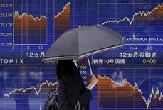 Женщина с зонтом у брокерской конторы в Токио. 20 мая 2015 года. Азиатские фондовые рынки, кроме Гонконга, выросли в среду за счет экономической статистики и местных новостей. REUTERS/Yuya Shino
