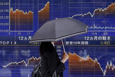 Un peatón que sostiene un paraguas camina junto a un tablero electrónico que muestra las gráficas de fluctuación del índice Nikkei de la Bolsa de Tokyo, en Tokyo, Japón, 20 de mayo de 2015. Las bolsas de Asia caían el miércoles después de una jornada dispar en Wall Street, aunque el reporte de un crecimiento económico mejor que lo esperado en Japón impulsó al Nikkei a un máximo en 15 años. REUTERS/Yuya Shino