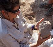 Archaeologist Sonia Harmand examines a stone tool discovered in desert badlands near Lake Turkana in northwestern Kenya, in this undated handout photo provided by MPK-WTAP. REUTERS/MPK-WTAP/Handout via Reuters