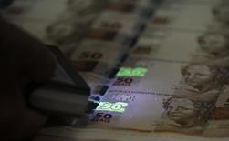 Funcionário verifica folhas de papel-moeda durante visita da mídia à Casa da Moeda. 23/08/2012 REUTERS/Sergio Moraes