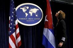 Funcionária coloca bandeiras de Estados Unidos e Cuba em sala de imprensa antes de entrevista coletiva em Washington. 22/05/2015 REUTERS/Yuri Gripas