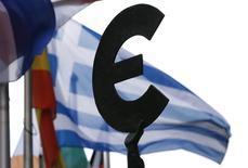 Grecia no puede realizar el pago de deuda al Fondo Monetario Internacional previsto para el próximo mes a menos de que llegue a un acuerdo con los acreedores, dijo el domingo el ministro del Interior del país, en las declaraciones más explícitas de Atenas sobre la posibilidad de que caiga en un default. En la imagen, una bandera griega tras una estatua con el símbolo del euro en el exterior del Parlamento Europeo en Bruselas, Bélgica, el 20 de mayo de 2015.  REUTERS/Francois Lenoir
