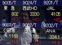 Un peatón se refleja en un tablero electrónico que muestra varios índices de precios, afuera de una agencia de la bolsa, en Tokyo, Japón. 20 de mayo de 2015. Las bolsas de Asia subían el lunes, pero las ganancias eran limitadas por las preocupaciones de que la volatilidad del mercado podría intensificarse en momentos en que el banco central de Estados Unidos se prepara para subir las tasas de interés por primera vez en seis años. REUTERS/Yuya Shino