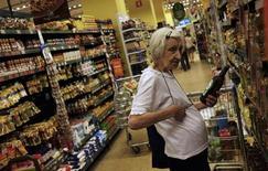 Una clienta elige una botella de aceite de oliva, en un supermercado en Sao Paulo, 10 de enero de 2014. La economía de Brasil probablemente se contraiga más de lo previsto anteriormente y enfrentará una inflación más alta este año, según el sondeo semanal Focus del Banco Central publicado el lunes. REUTERS/Nacho Doce